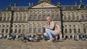 Una mujer joven está alimentando palomas en el centro de Amsterdam en cuadrado de la presa Turismo en Europa y el concepto holand almacen de metraje de vídeo