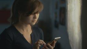 Una mujer joven está correspondiendo en el teléfono en casa, la muchacha se está divirtiendo en Internet, pero es distraída por u