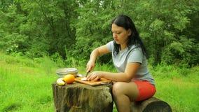 Una mujer joven está cortando una manzana en las rebanadas para una ensalada de fruta para el desayuno en naturaleza metrajes