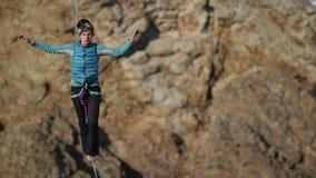 Una mujer joven está en el slackline en la mucha altitud almacen de metraje de vídeo