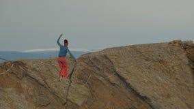 Una mujer joven está en el slackline en la mucha altitud almacen de video