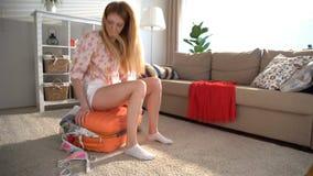Una mujer joven está intentando cerrar una maleta anaranjada hasta los topes almacen de metraje de vídeo