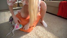 Una mujer joven está intentando cerrar una maleta anaranjada hasta los topes almacen de video
