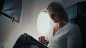 Una mujer joven está leyendo una revista en la carlinga de un aeroplano Comodidad y entretenimiento en el viaje almacen de video