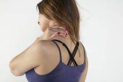 Una mujer joven está luchando con dolor, en fondo Foto de archivo libre de regalías