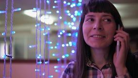Una mujer joven está utilizando un teléfono cerca de una guirnalda eléctrica azul almacen de metraje de vídeo