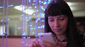 Una mujer joven está utilizando un teléfono cerca de una guirnalda eléctrica azul metrajes