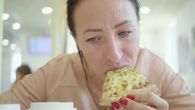 Una mujer joven est? comiendo un pedazo de pizza Risa feliz encantadora de la muchacha y el morder de rebanada grande de pizza he almacen de video