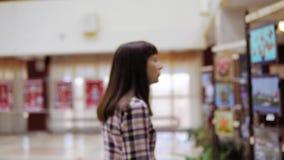 Una mujer joven examina la exposición en la galería almacen de metraje de vídeo