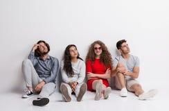 Una mujer joven feliz con un grupo de amigos aburridos que se sientan en un piso fotografía de archivo