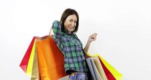 Una mujer joven feliz que sostenía mucho coloreó bolsos con nueva ropa en casa metrajes