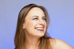 Una mujer joven fervientemente y ríe sinceramente en un fondo de la lila Fotografía de archivo libre de regalías