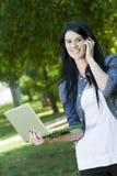 Una mujer joven habla en el teléfono con el ordenador Foto de archivo
