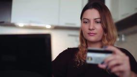 Una mujer joven hermosa compra los regalos con una tarjeta de crédito Estilo casero almacen de metraje de vídeo