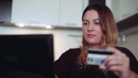 Una mujer joven hermosa compra los regalos con una tarjeta y un ordenador de crédito Estilo casero almacen de metraje de vídeo