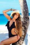 Una mujer joven hermosa con el pelo largo en un sombrero de paja se relaja encendido fotografía de archivo