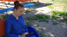 Una mujer joven hermosa con el pelo rojo en un vestido del dril de algodón y las pecas en su cara se sienta en el parque en un ba almacen de metraje de vídeo