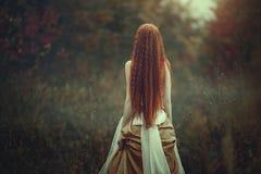 Una mujer joven hermosa con el pelo rojo muy largo como bruja camina con la opinión de la parte posterior del bosque del otoño