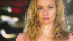 Una mujer joven hermosa con el pelo rubio se está colocando en un espacio abierto en un día ventoso que mira atento la cámara cop metrajes