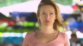 Una mujer joven hermosa con el pelo rubio se está colocando en un espacio abierto en un día ventoso que mira atento la cámara cop almacen de video