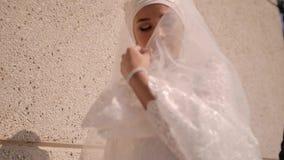 Una mujer joven hermosa cubre su cara con su vestido blanco como la nieve y se abre la cara otra vez almacen de metraje de vídeo