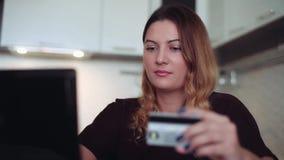 Una mujer joven hermosa en ropa oscura compra regalos con una tarjeta de crédito y un ordenador Estilo casero metrajes