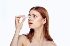 Una mujer joven hermosa en un fondo blanco aislado observa las mordeduras, farmacia Fotografía de archivo