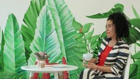 Una mujer joven, hermosa en un traje rayado está bebiendo el café contra un fondo de hojas verdes metrajes
