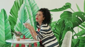 Una mujer joven, hermosa en un traje rayado que sostiene una taza de café metrajes