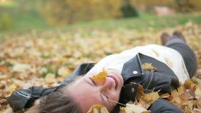 Una mujer joven hermosa miente en follaje amarillo debajo de un árbol almacen de metraje de vídeo