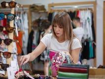 Una mujer joven hermosa que elige la banda en una tienda, accesorios hermosos del pelo para las mujeres en un fondo ligero borros Fotos de archivo