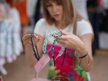 Una mujer joven hermosa que elige la banda en una tienda, accesorios hermosos del pelo para las mujeres en un fondo ligero borros Imagenes de archivo
