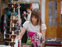 Una mujer joven hermosa que elige la banda en una tienda, accesorios hermosos del pelo para las mujeres en un fondo ligero borros Foto de archivo libre de regalías