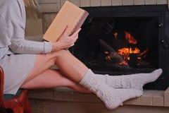 Una mujer joven hermosa que lee un libro y que relaja el goce cerca de una chimenea Devanadera acogedora Concepto de los días de  Imagenes de archivo