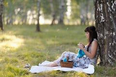 Una mujer joven hermosa que se inclina contra un árbol hace punto Imagen de archivo libre de regalías