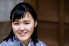 Una mujer joven hermosa que sonríe en la cámara que lleva un kimono foto de archivo libre de regalías