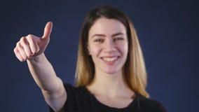 Una mujer joven hermosa que sonríe y que muestra los pulgares para arriba almacen de metraje de vídeo