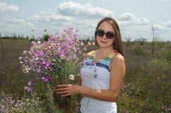 Una mujer joven hermosa recoge las flores salvajes Fotos de archivo libres de regalías