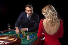 Una mujer joven hermosa y un hombre se están sentando en una tabla de la ruleta casino fotografía de archivo libre de regalías