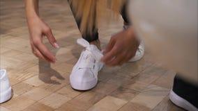 Una mujer joven implica sus cordones en las zapatillas de deporte blancas en una tienda almacen de metraje de vídeo