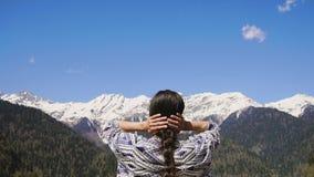 Una mujer joven inhala el aire limpio y fresco de la montaña en una reserva de naturaleza almacen de video