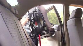 Una mujer joven instala un asiento de la seguridad del niño con el soporte de ISOFIX en el coche metrajes
