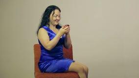 Una mujer joven lee un mensaje en su teléfono y que la levanta alegre soñador que los ojos hacia arriba observan metrajes