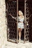 Una mujer joven lleva a cabo sus manos detrás de las barras la puerta Foto de archivo
