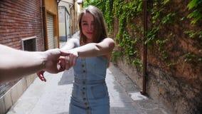 Una mujer joven lleva a su novio por una mano a través de una calle en Italia metrajes