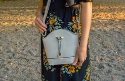 Una mujer joven, llevando un vestido de flores, sosteniendo un mini bolso Fotografía de archivo