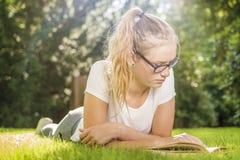 Una mujer joven miente en la hierba en el parque y mira en un libro imagenes de archivo