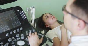 Una mujer joven miente en un sofá en el cuarto del diagnóstico del ultrasonido almacen de metraje de vídeo