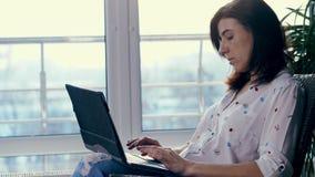Una mujer joven, una muchacha, una morenita, en la camisa blanca y vaqueros, se está sentando en silla, con el ordenador portátil almacen de video