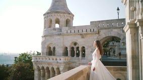 Una mujer joven o una novia muy hermosa en un vestido blanco, camina el balcón del castillo viejo, y miradas en cómo el novio almacen de metraje de vídeo